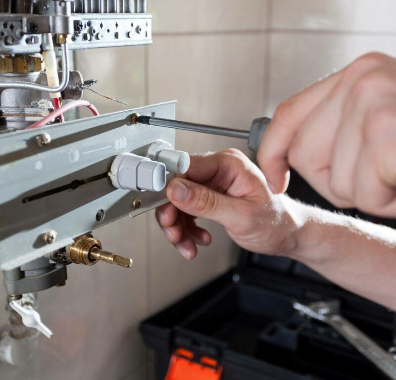 Boiler repair man turning screws on boiler interface