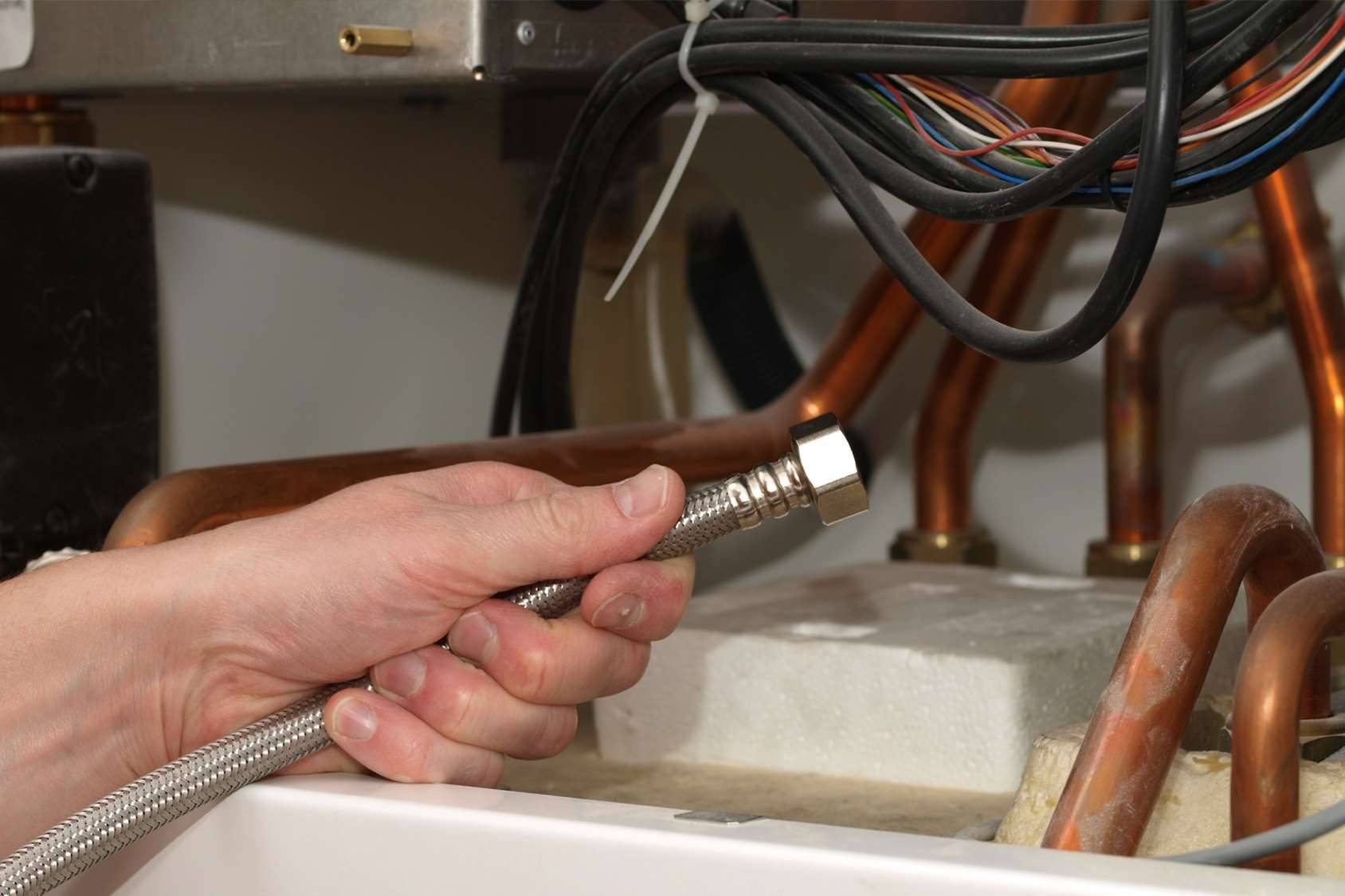 Man hand with cable inside the condensing boiler