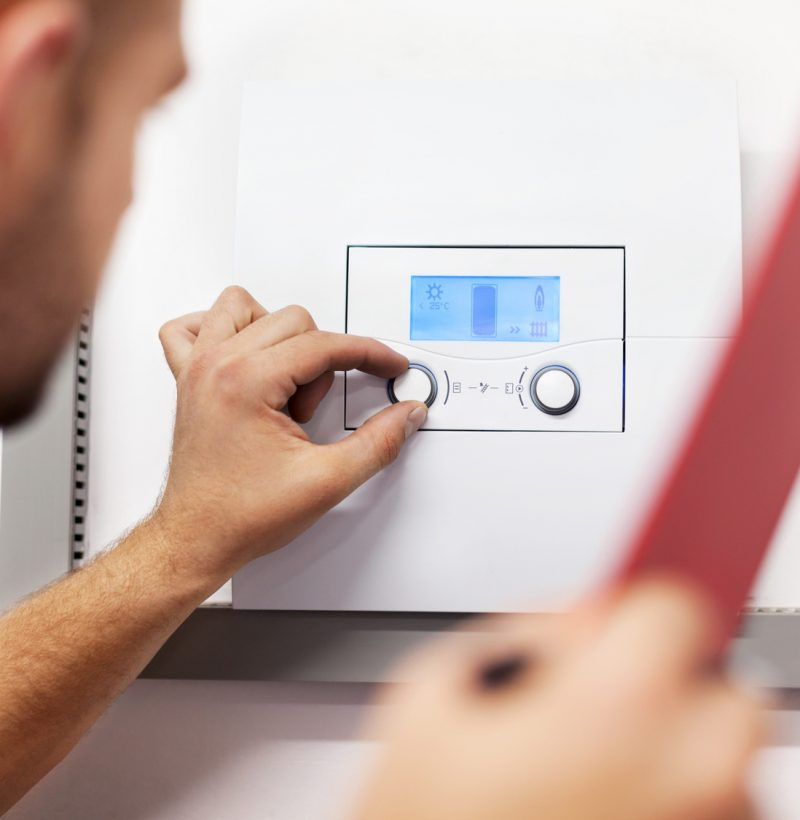 Repair man changing boiler settings using dials